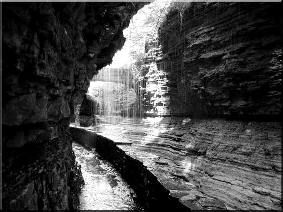 A photograph taken from underneath Rainbow Falls, Watkins Glen State Park in New York.