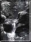 Black and white photograph of a series of small waterfalls in upper Buttermilk Falls gorge.