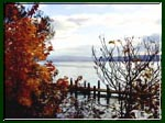 A photo taken of a dock in autumn on Cayuga Lake with Ithaca, New York in the distance.