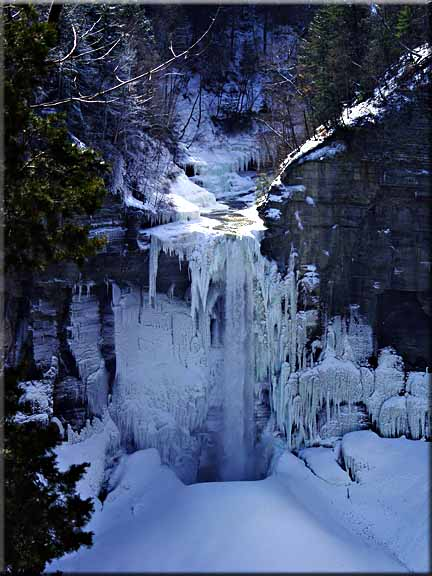 The winter sun streams over the top of a frozen taughannock Falls.