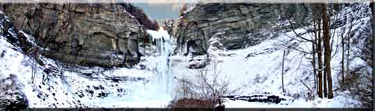 A panoroma photograph of Taughannock Falls frozen in winter.